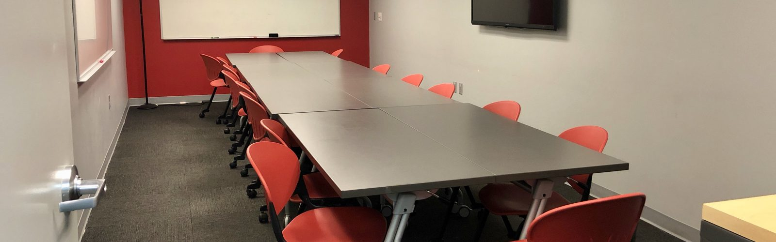 small conference room with about a dozen red chairs, a board to write on, and one screen.